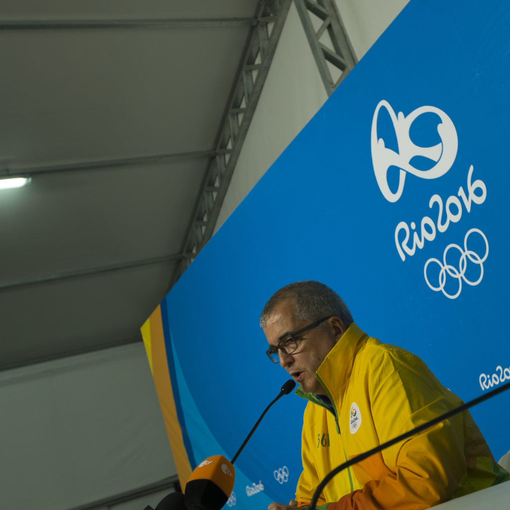 Olympic Games, Rio de Janeiro Mario Andrade, Director of Communications for Rio 2016 commenting on the stray bullet that entered the press tent in Deodor earlier on Saturday. In the background is the actual entry hole of the bullet, not clearly visible.